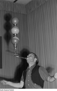 man balancing balls and glasses on a rod from his mouth