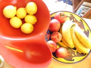 lemons, bananas, nectarines, peaches a tomato in fruit bowls