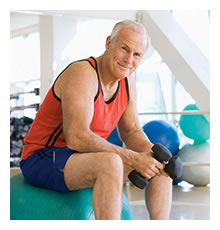 gentleman sitting on exercise ball with weights