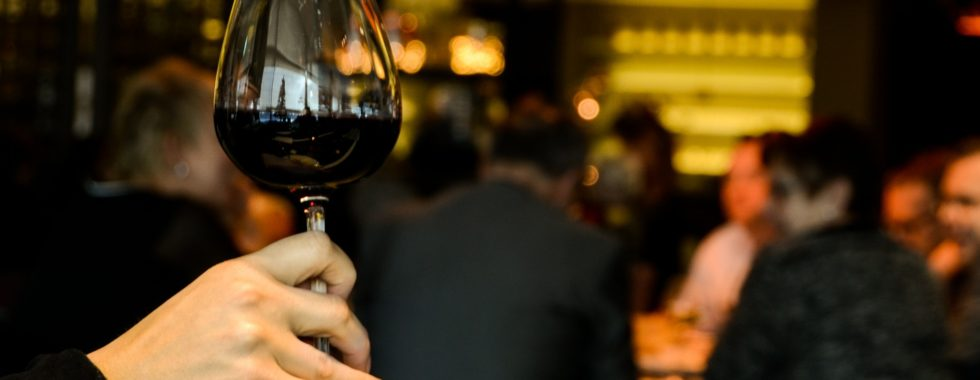 benefits of red wine - woman holding wine in a restaurant